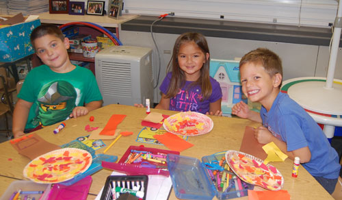 Kindergartners making paper plate trees and leaves for Autumn