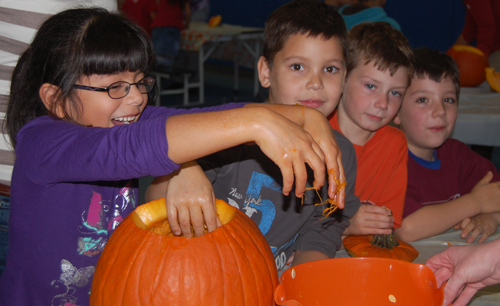 Students cleaning out a pumpkin