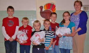 Conestoga ES students, from left, Daniel Hess, Trevor Adams, Miles Sandt, Gabriel Midile, Joseph Greer and Melissa Weaver display three of the donated turkeys with their principal, Tamara Baker.