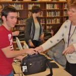 Sophomore Daniel Bleacher gets his new laptop from district technology analyst Shelby Foster.