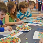 Hambright first-graders count out 100 cereal pieces for their necklaces.