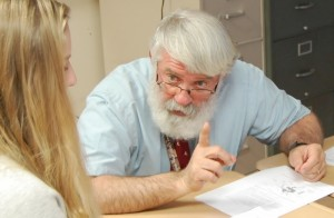 Teacher Joe Herman gestures as he talks with a student.