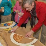 Teacher Mindy Swope uses a protractor to measure a pizza slice.