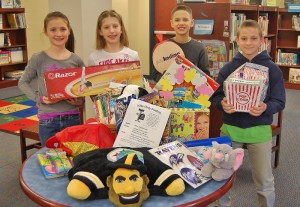 From left, Central Manor fourth-graders Morgan Miller, Emily Riggs, Javin Vassor and Leif Heckaman pose with some of the items that will be up for auction Sunday.