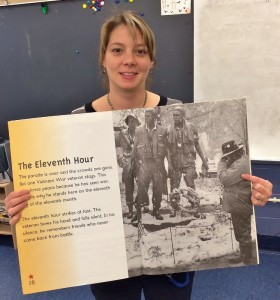 "Jenny Steffy holds a photo of her uncle in a children's book titled ""Veterans Day."""