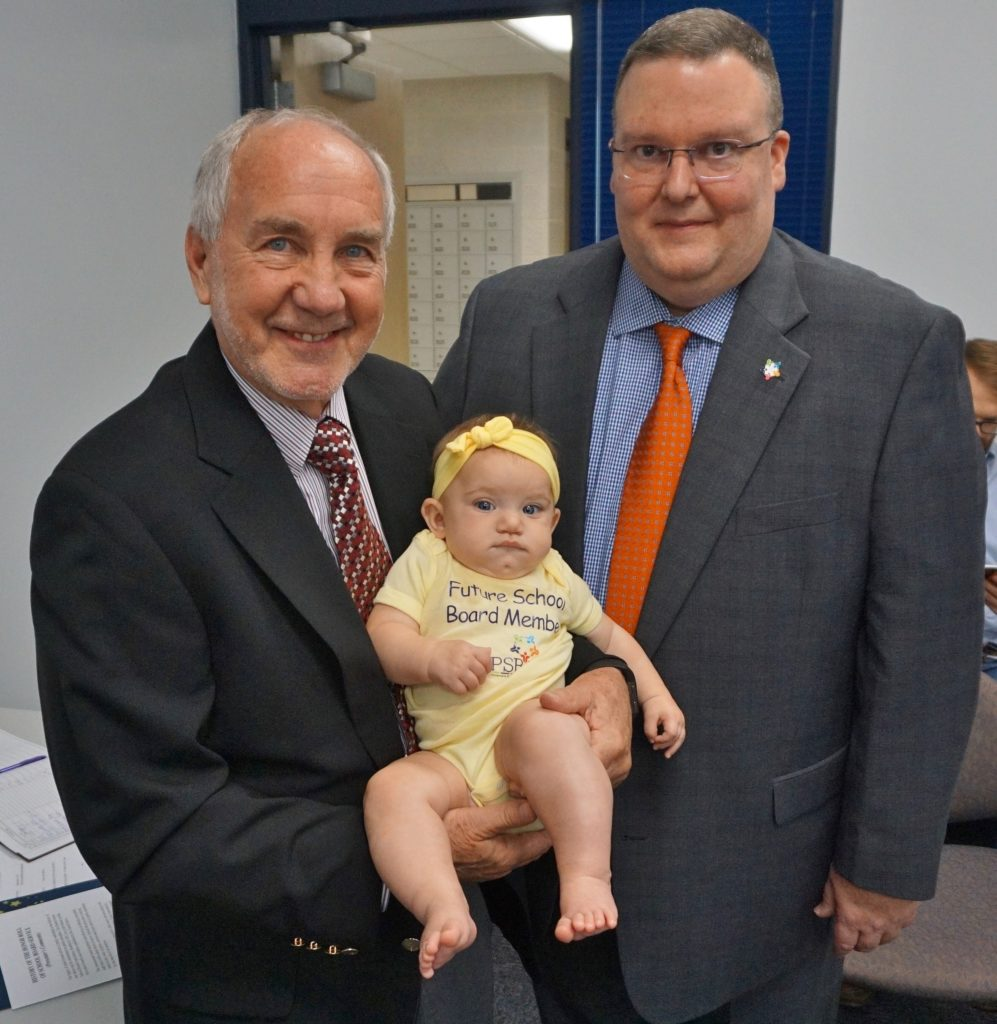 Board member holding grandchild.