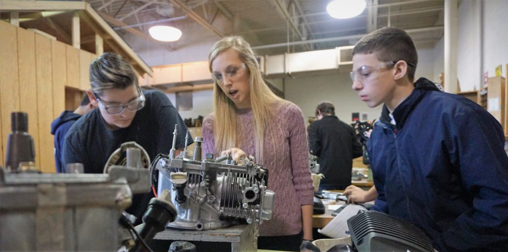 Meagan Slates works with students on a small engine repair lab.