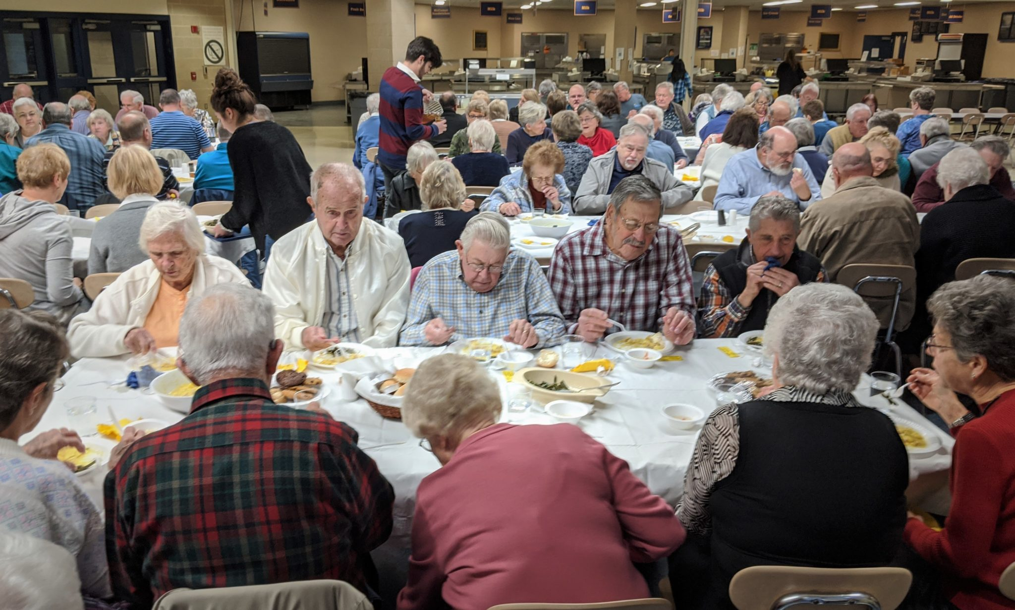 Senior citizens eating dinner in cafeteria.