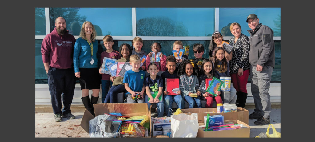 Students, principals and business representatives with school supplies.