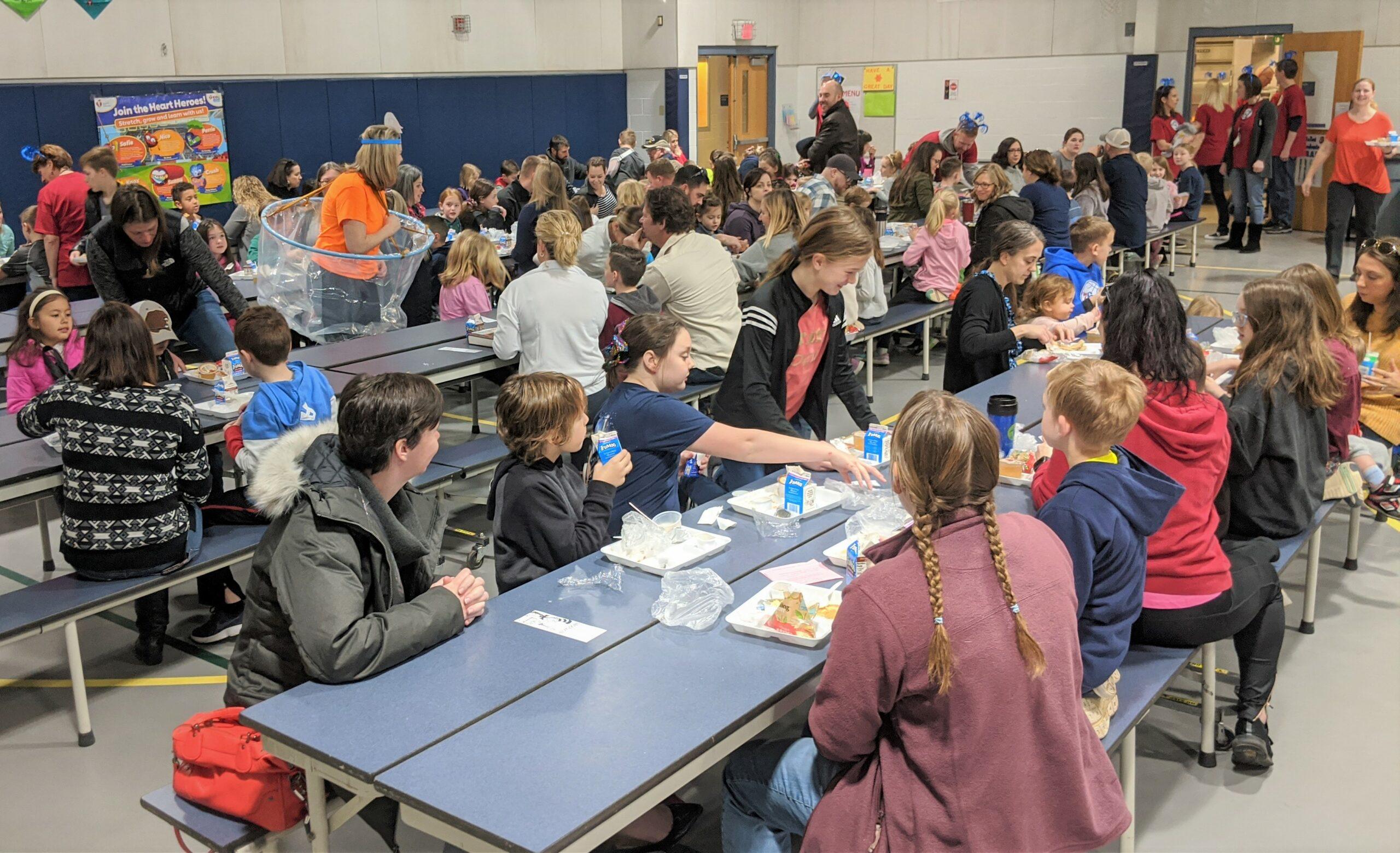 Community members eat breakfast in the multipurpose room