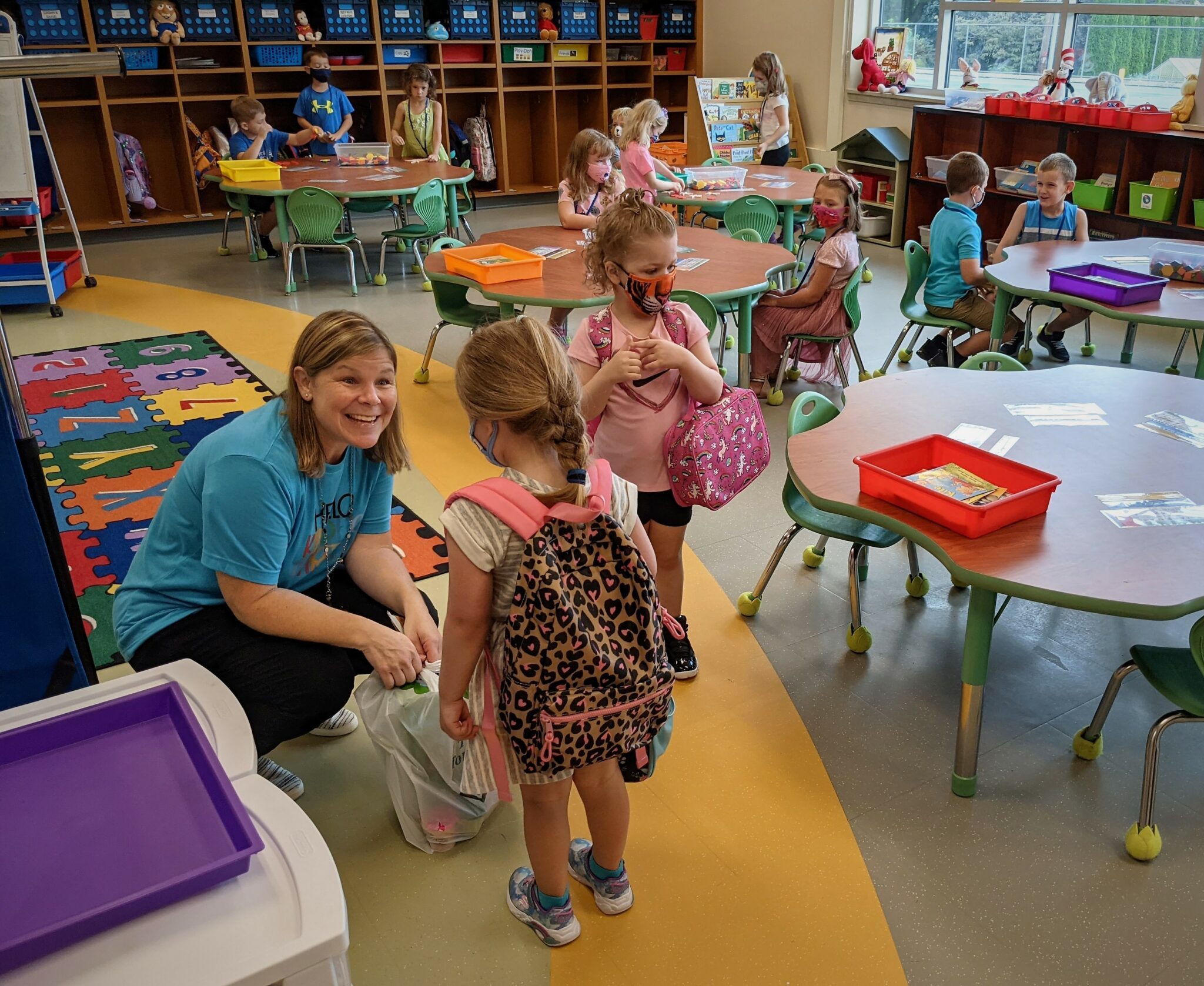 A teacher greets a student at Conestoga Elementary