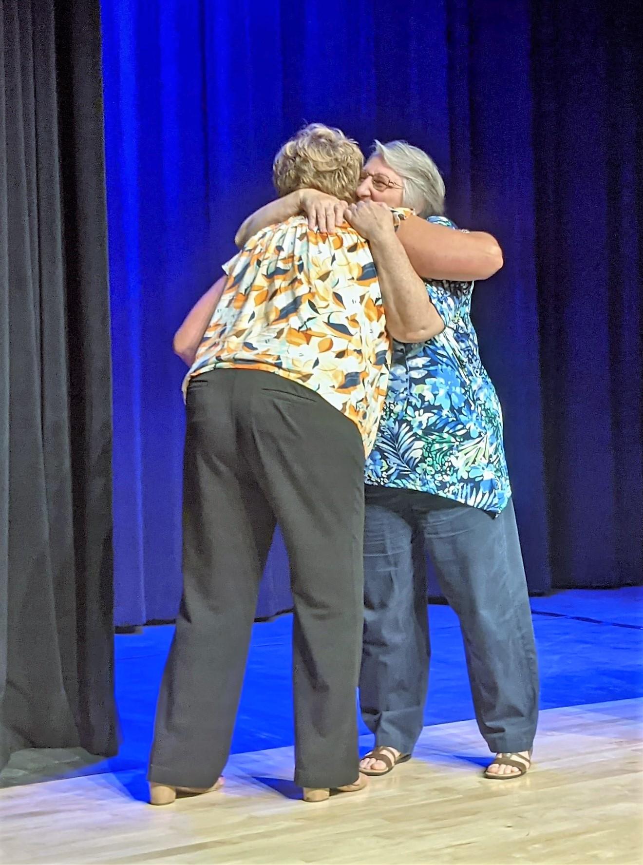 Letort principal Carly McPherson congratulates school secretary Mary Jacoby.